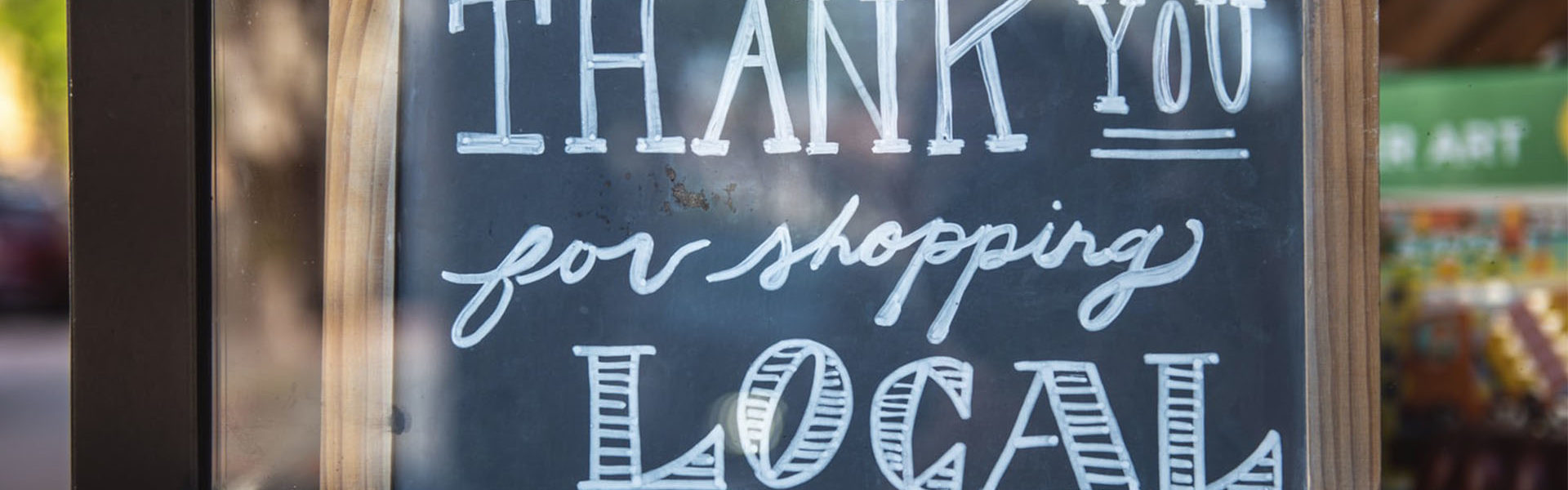 """Chalk born sign that reads """"thank you for shopping local"""""""